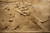 stock photo of babylonia  - Old relief representing an assyrian warrior hunting lions - JPG