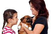 A girl, her mother and a pekingese dog isolated on a white background