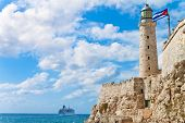 The castle of El Morro in the bay of Havana with a waving cuban flag and a tourism cruiser ship in t