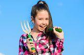 Kid Cheerful Gardener Holds Rake And Cucumber Blue Sky Background. Girl Gardener With Hand Rake. Gar poster