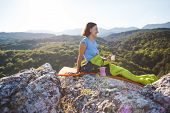 A Woman Is Drinking Coffee While Sitting On Top Of A Mountain. A Girl In A Sleeping Bag Drinks A Hot poster