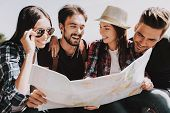 Group Of Young Smiling People Holding Paper Map. Casualy Dressed Happy Travelers With Backpacks Plan poster