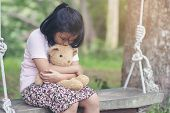 Sad Child Hugging Teddy Bear On Wooden Swing In Park.asian Little Girl Sitting With Best Friends For poster