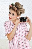 Portrait of beautiful young woman with hair curlers holding an old fashioned digital camera