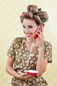 Portrait of an attractive young woman with hair curlers holding toy phone over a textured background