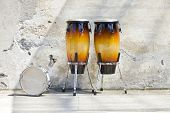two congas in front of a vintage wall