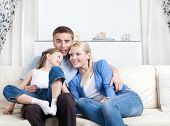 foto of nuclear family  - Nuclear family laugh sitting on the white couch in the living room - JPG