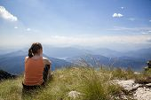 pic of mountain chain  - Woman sitting on mountain top of Monte Generoso admiring mountain landscape around Lugano lake and blue sky - JPG