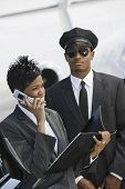 An African American business woman using cell phone while driver standing in the background at airfi
