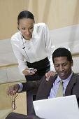 Happy business woman using cell phone and man using laptop