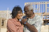 Happy loving senior African American couple in front of incomplete house