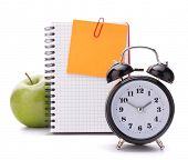 Alarm clock, blank notebook sheet and apple. Schoolchild and student studies accessories. Back to sc