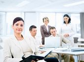picture of work crew  - Group of five young business people working at office with businesswoman sitting in front - JPG