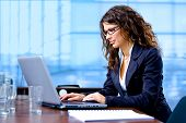 pic of people work  - Happy young businesswoman working on laptop computer at office smiling - JPG