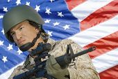 Soldier with assault rifle in front of US flag