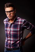 Young casual man in a squared shirt and eyeglasses is holding his jeans at the back and is looking seriously at the camera. over black background