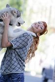 young happy woman playing with haski dog outdoors
