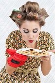 Young woman in dress with hair curlers smelling a plate of fresh baked cookies