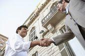 Twee zakenlieden schudden handen voor een succesvolle omgaan met het gebouw op de achtergrond