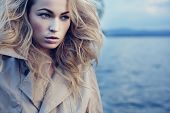 Beautiful young blond woman outdoors portrait near the lake