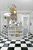 Bright White Clean Kitchen With Black And White Checkered Tiled Floor And Hanging Pans.