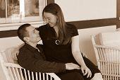 Joven sonriente pareja sentados juntos en el sofá de dos plazas