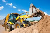 stock photo of bulldozer  - Excavator machine unloading sand during earth moving works at construction site - JPG