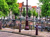 image of old bridge  - Bicycles along a bridge over the canals of Amsterdam - JPG