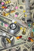 Stethoscope With Hypodermic Syringe And Doze Of Medical Tablets On U.s. Dollar Banknotes