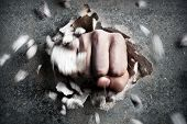 stock photo of anger  - a wall is broken through by a fist - JPG