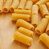 a pile of uncooked penne rigate on a table, ready to be boiled