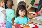 stock photo of supervision  - Elementary Pupils Collecting Healthy Lunch In Cafeteria - JPG