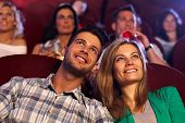 stock photo of cinema auditorium  - Happy young couple watching movie in cinema - JPG