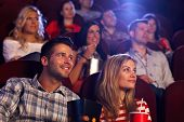 stock photo of cinema auditorium  - Young people sitting at auditorium of movie theater - JPG