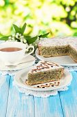 Delicious poppy seed cake with cup of tea on table on bright background