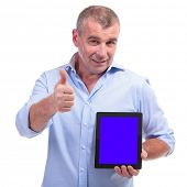 casual senior man presenting a tablet with an empty blue screen and showing the thumbs up gesture wh