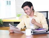 Happy asian young business man read newspaper and smile