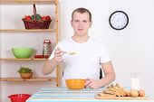 Man Eating Corn Flakes With Milk In The Kitchen