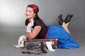 Funny Pinup Girl Lying On Overfilled Suitcase