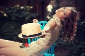 young woman in elegant dress sit on chair in garden with hat in hand summer day