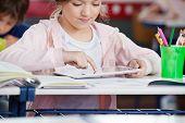 Little schoolgirl using digital tablet at desk in classroom