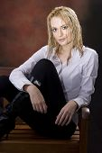 picture of wet pants  - Curly blond with tight pants wearing black boots sitting in chair with wet hair - JPG