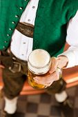 Man in Bavarian Tracht, a brewer, with beer stein in brewery