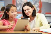 stock photo of teachers  - Pupils In Class Using Digital Tablet With Teacher - JPG