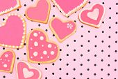stock photo of poka dot  - Hand decorated heart shaped cookies on pink patterned background - JPG