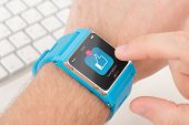 pic of watch  - Male finger taps like icon on blue smart watch - JPG
