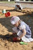 Little Girl In Dress Plays In Sandbox With Shovel On Summer Day.