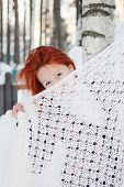 Redhead Girl Hides Her Face Behind Shawl Near Birch At Winter Day.