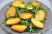 Fried potatoes with green rocket salad