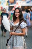German Woman wearing a traditional Dirndl and eating candyfloss